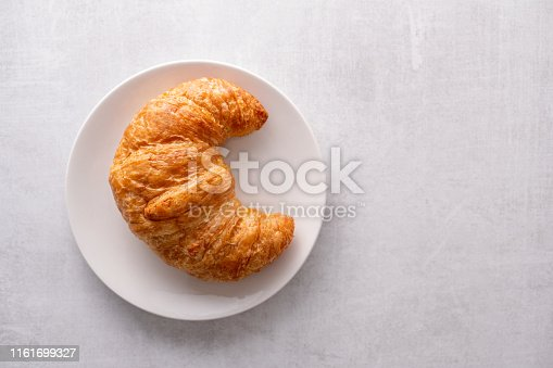 Warm crispy flaky croissant roll on white plate and distressed table
