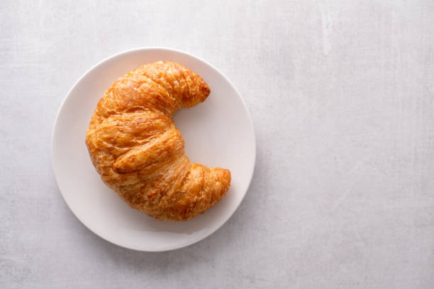 Warm crispy flaky croissant roll on white plate and distressed table Warm crispy flaky croissant roll on white plate and distressed table croissant stock pictures, royalty-free photos & images