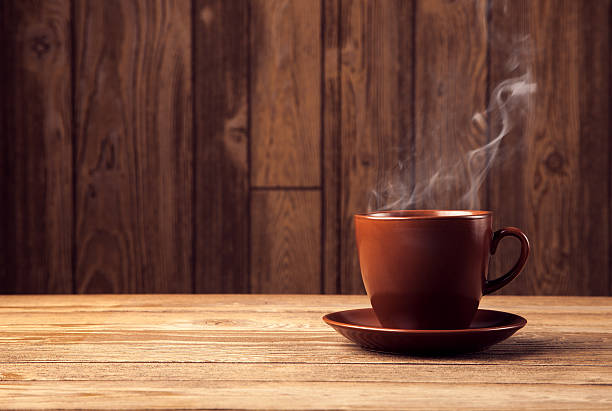 warm cup of coffee on brown background stock photo