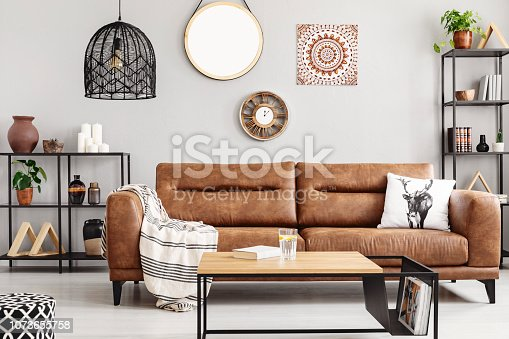 istock Warm ethno living room with big comfortable leather couch and metal furniture, real photo 1073655758