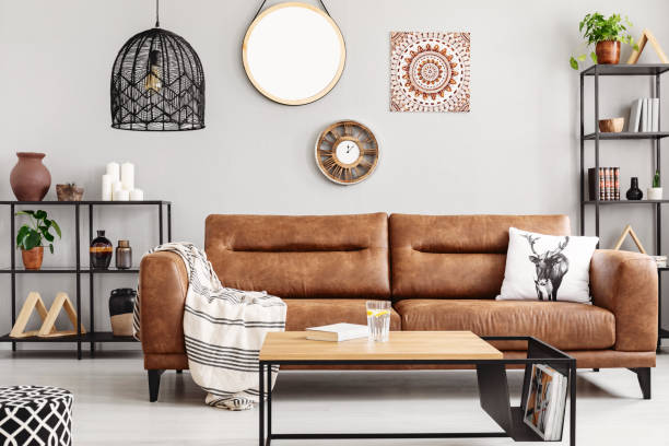 Warm ethno living room with big comfortable leather couch and metal furniture, real photo Warm ethno living room with big comfortable leather couch and metal furniture, real photo scandinavian culture stock pictures, royalty-free photos & images