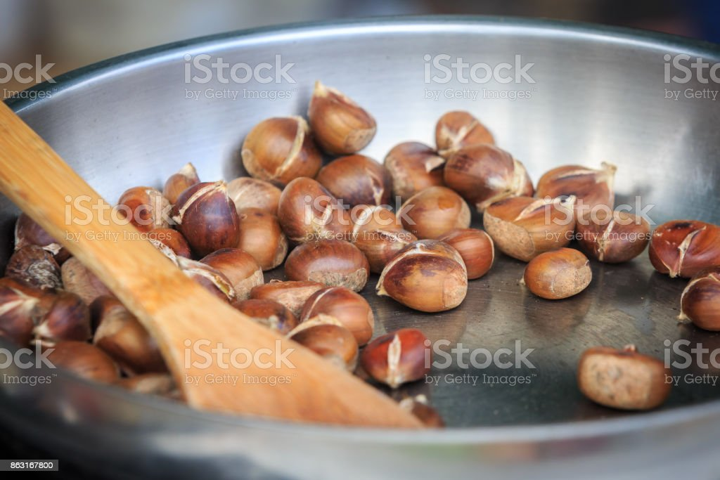 Warm fried edible chestnuts (castanea sativa) lie in a frying pan stock photo