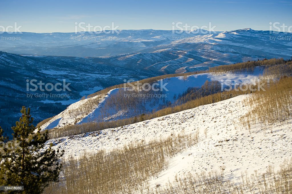 Warm Golden Light and Blue Mountain Shadows in Winter Landscape stock photo