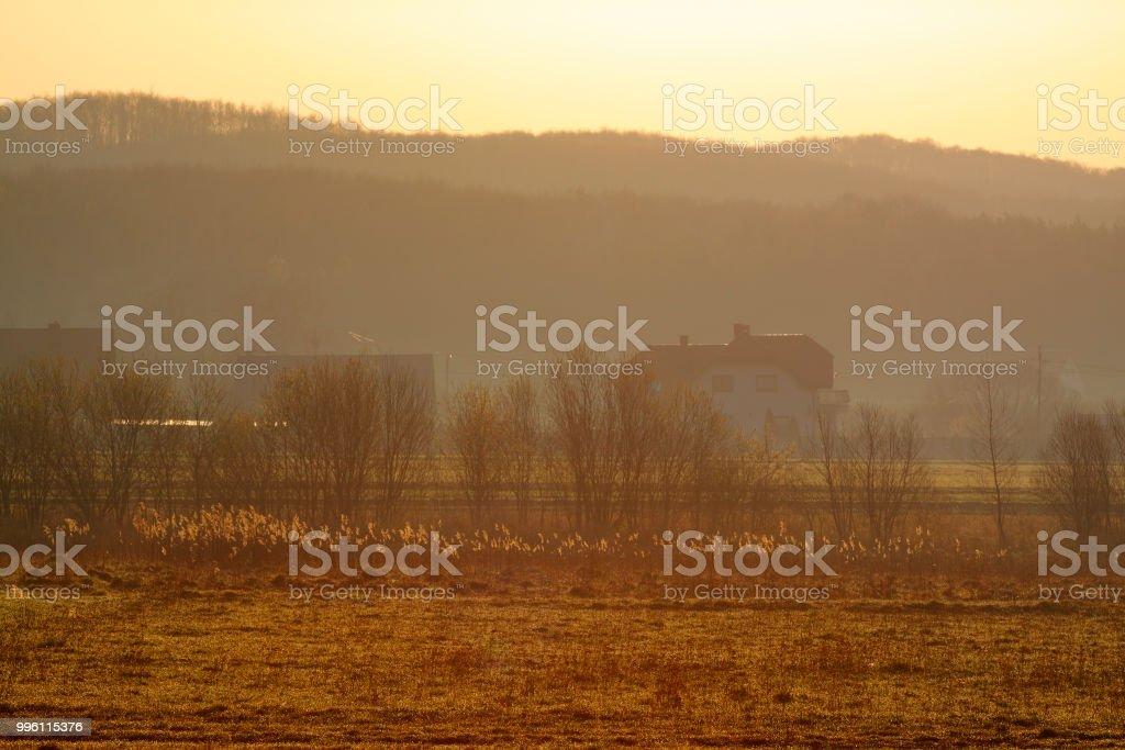 Warm hazy sunrise over village stock photo