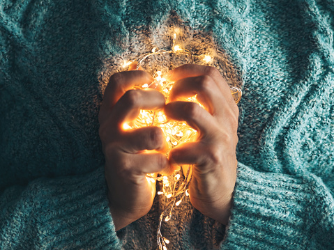 Warm heart, love concept. Women's hands holding a garland. Girl in a blue sweater with Christmas lights in her hands