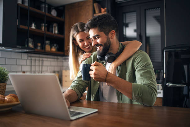 Warm home atmosphere Happy modern couple doing online shopping in the kitchen. Excited women is embracing her man happy couple stock pictures, royalty-free photos & images