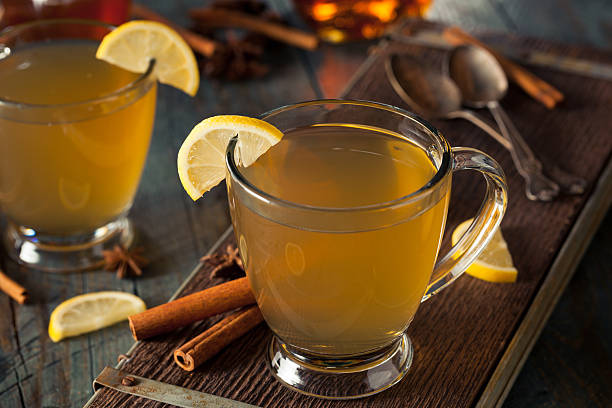 Warm Hot Toddy with Lemon Warm Hot Toddy with Lemon Bourbon and Spices hot apple cider stock pictures, royalty-free photos & images