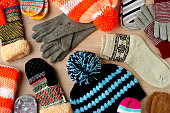 Caps, mittens, gloves and socks for cold seasons. Warm autumn and winter clothes. View from above.