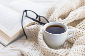 Warm knitted plaid, glasses, cup of hot coffee and book