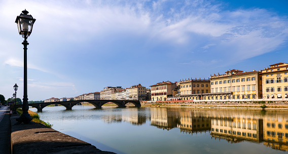 A warm late afternoon light illuminates the Arno riverbank in Florence