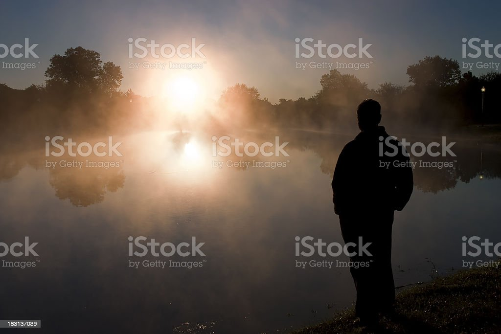 Warm Misty Sunrise Welcomes Silhouetted Male On Cool Fall Morning royalty-free stock photo