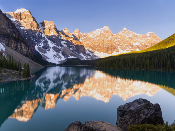 Warm Morning Sun Hitting Moraine Lake Mountains Sunrise at Moraine Lake, Banff National Park, Canada valley of the ten peaks stock pictures, royalty-free photos & images