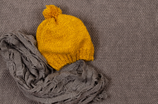 Warm mustard knitted beret and gray warm scarf. The concept of comfort and autumn warmth