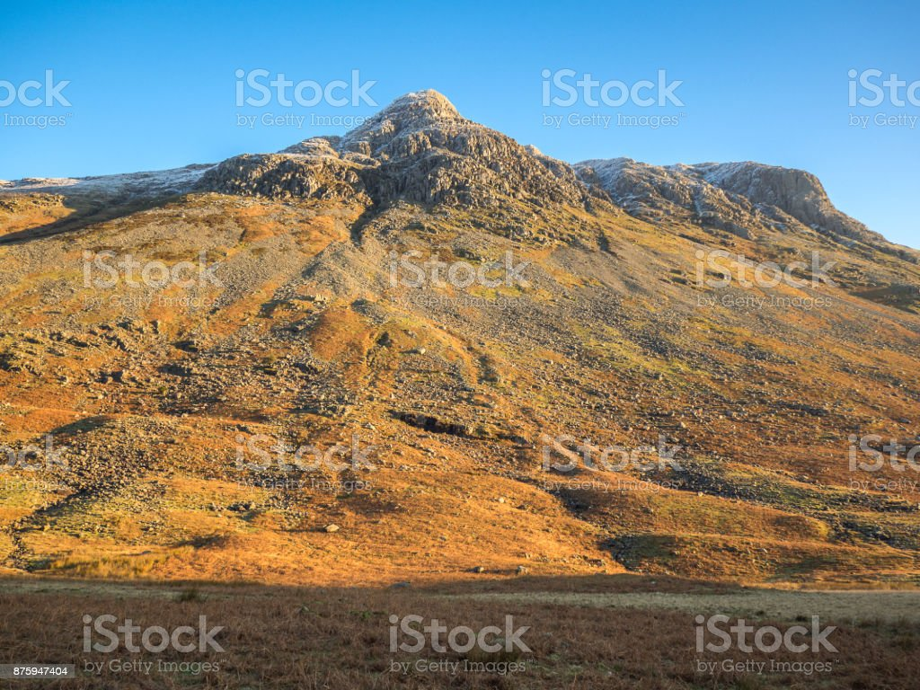 Warm orange glow of sunrise on Langdale Pikes, Lake District, Cumbria with clear blue sky stock photo