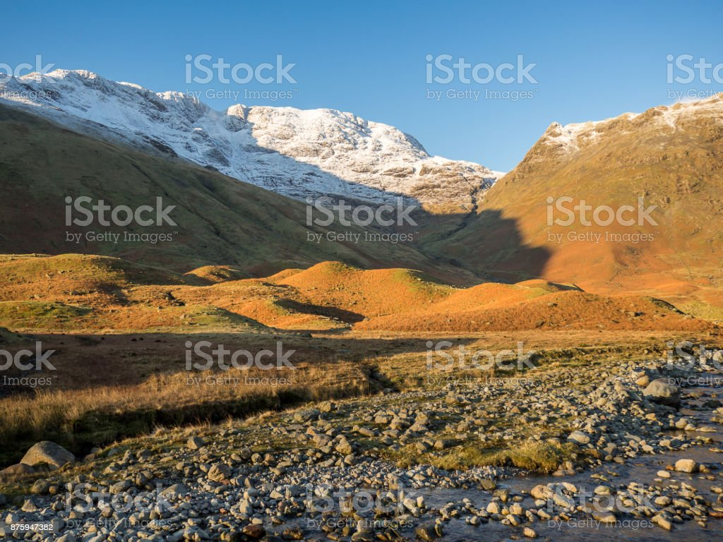 Warm orange glow on Langdale Valley Lake District Cumbria with snow capped mountains stock photo