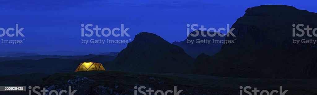 Warm orange tent camping in blue night mountain peaks Scotland royalty-free stock photo