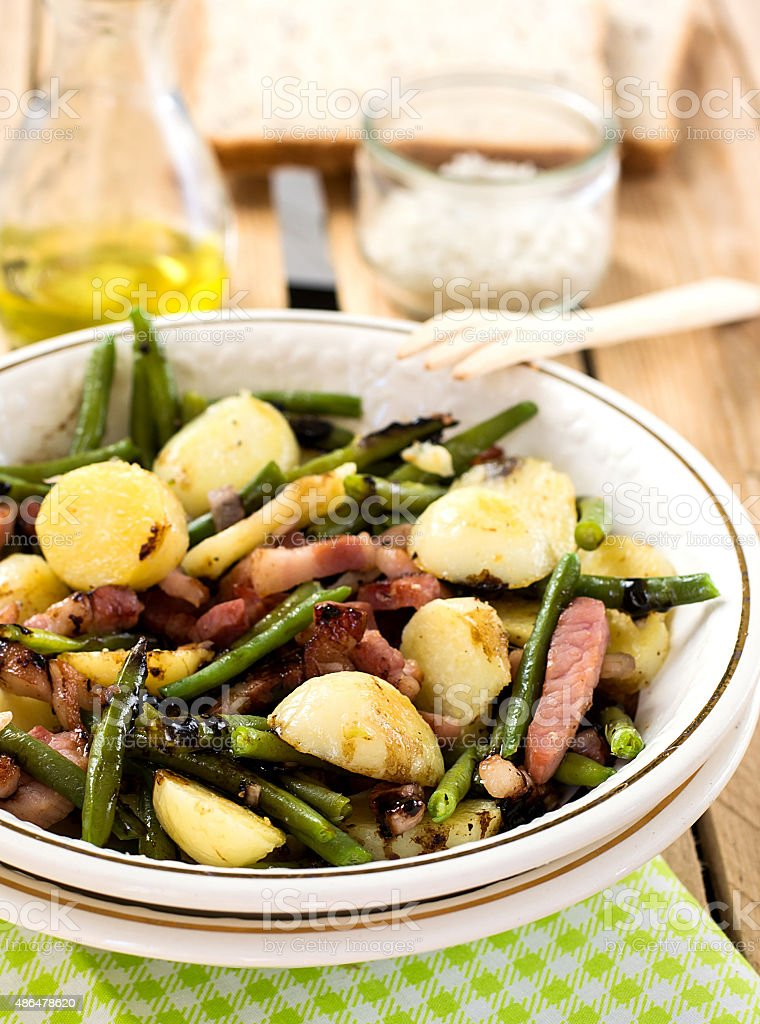 Warm potato salad with green beans and bacon stock photo