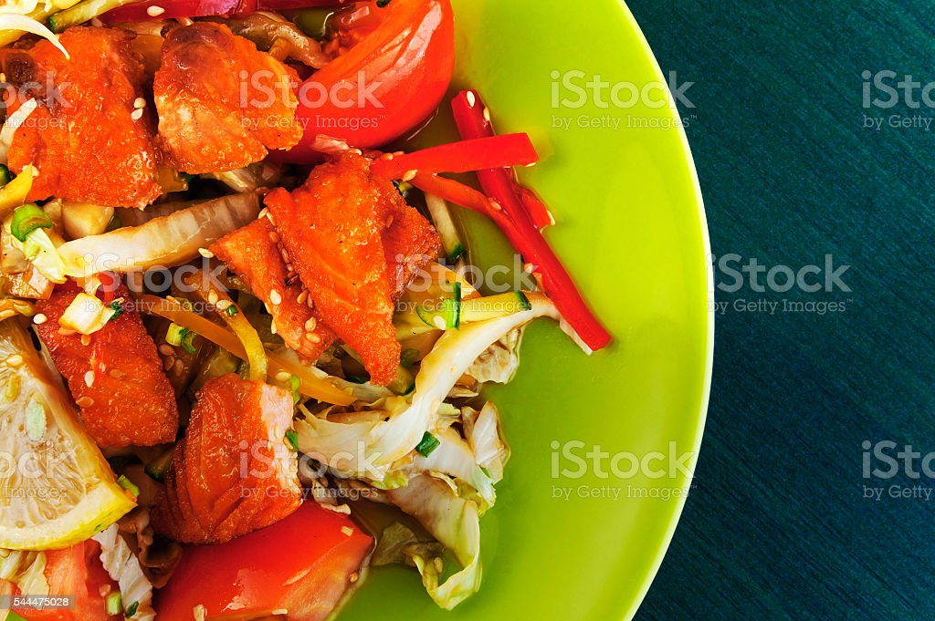 Warm salad with salmon and vegetables on a plate stock photo
