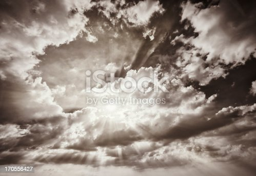 Monochrome image showing the sun creating rays of light fiiltering through clouds.