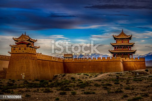 A beautiful sunset light over the Fort Jiayuguan under a moody sky in Gansu Province, Western China.