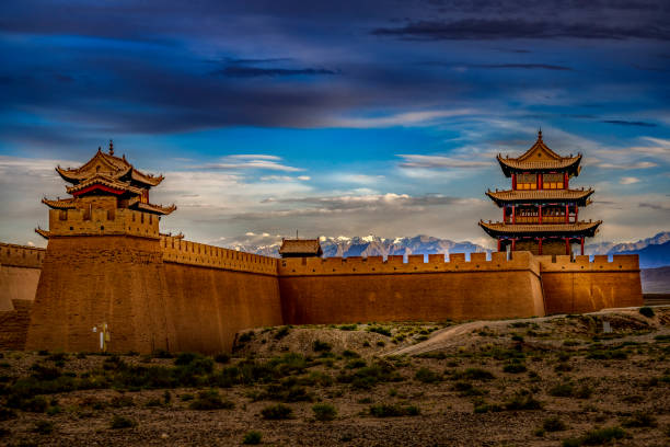 Warm Sunlight over the Fortress A beautiful sunset light over the Fort Jiayuguan under a moody sky in Gansu Province, Western China. ancient civilization stock pictures, royalty-free photos & images