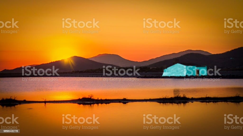warm sunset in the Balearic salinas with salt house in blue - foto stock