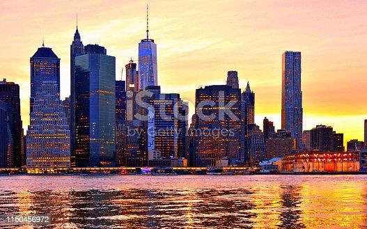 warm sunset on manhattan modern architecture skyline with moody reflections on Hudson river, Manhattan New York city