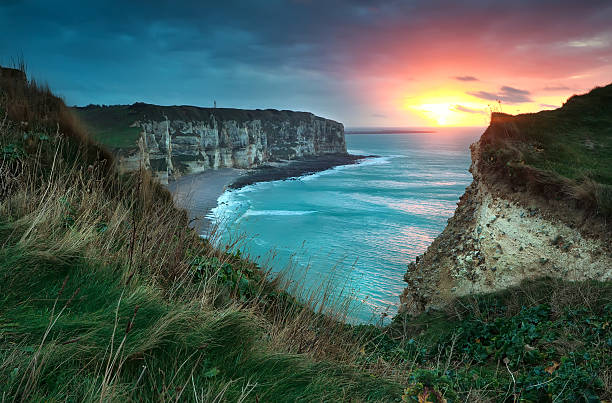 warm sunset over cliffs and ocean warm sunset over cliffs and ocean, Etretat, France dieppe france stock pictures, royalty-free photos & images