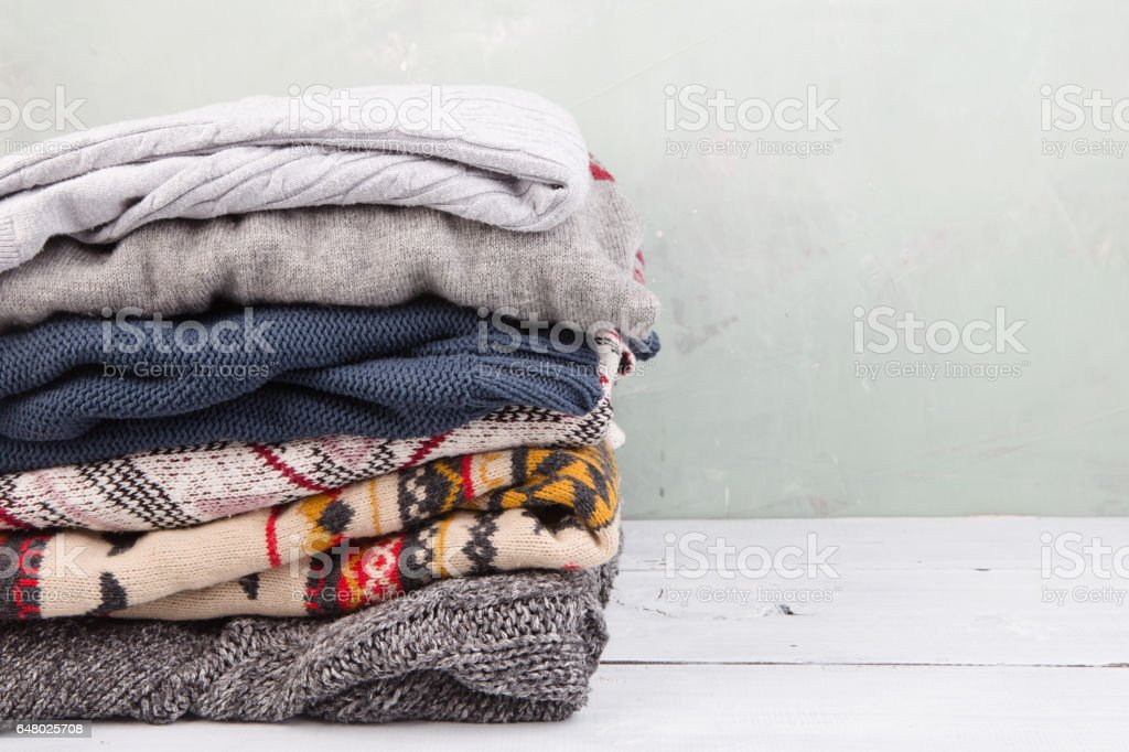warm sweaters stacked on wooden table stock photo