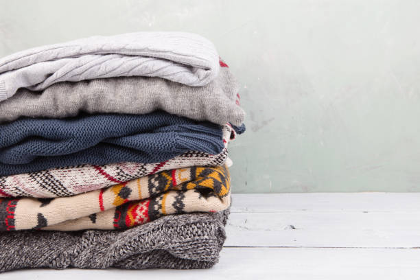 warm sweaters stacked on wooden table warm sweaters stacked on table warm clothing stock pictures, royalty-free photos & images