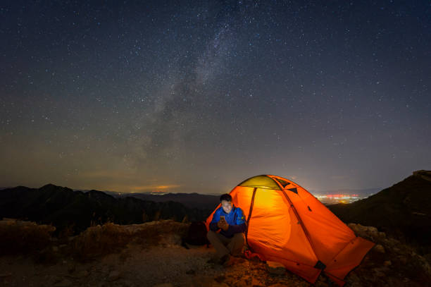 Warm tents under the Milky way, outdoor camping stock photo