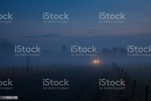 Photo of A warm winter's fog haunts the landscape of Jenksville, a small rural town in New York State, consisting of farms, open air,  two-lane country roads and headlights in the distant.