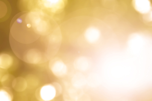 Warm yellow gold color of blurred sky background with nature glowing sun light flare and bokeh