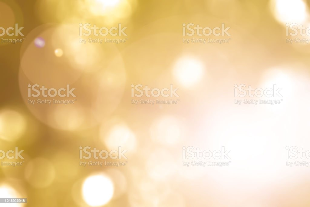 Warm yellow gold color of blurred sky background with nature glowing sun light flare and bokeh stock photo
