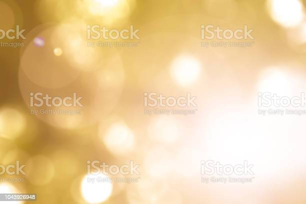 Photo of Warm yellow gold color of blurred sky background with nature glowing sun light flare and bokeh