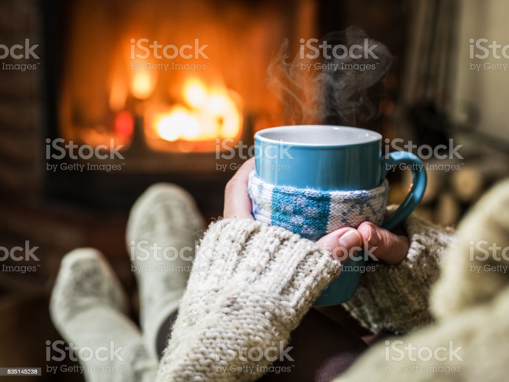 Warming and relaxing near fireplace with a cup of hot drink. - Foto stock royalty-free di Abiti pesanti