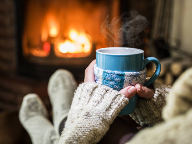 Warming and relaxing near fireplace with a cup of hot drink. stock photo