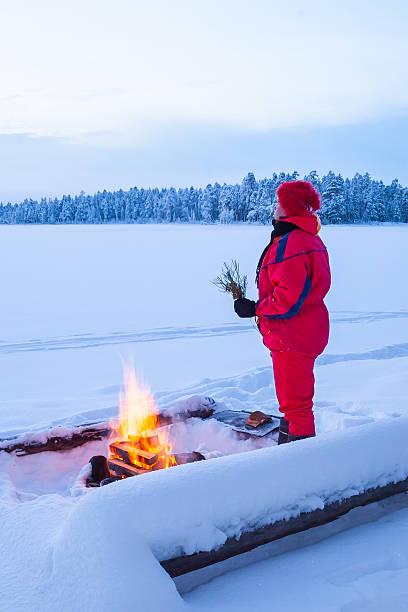 Warming at campfire stock photo