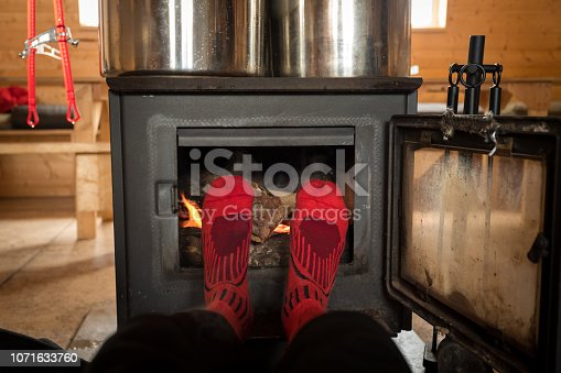Warming cold winter feet by the fire in a back country shelter