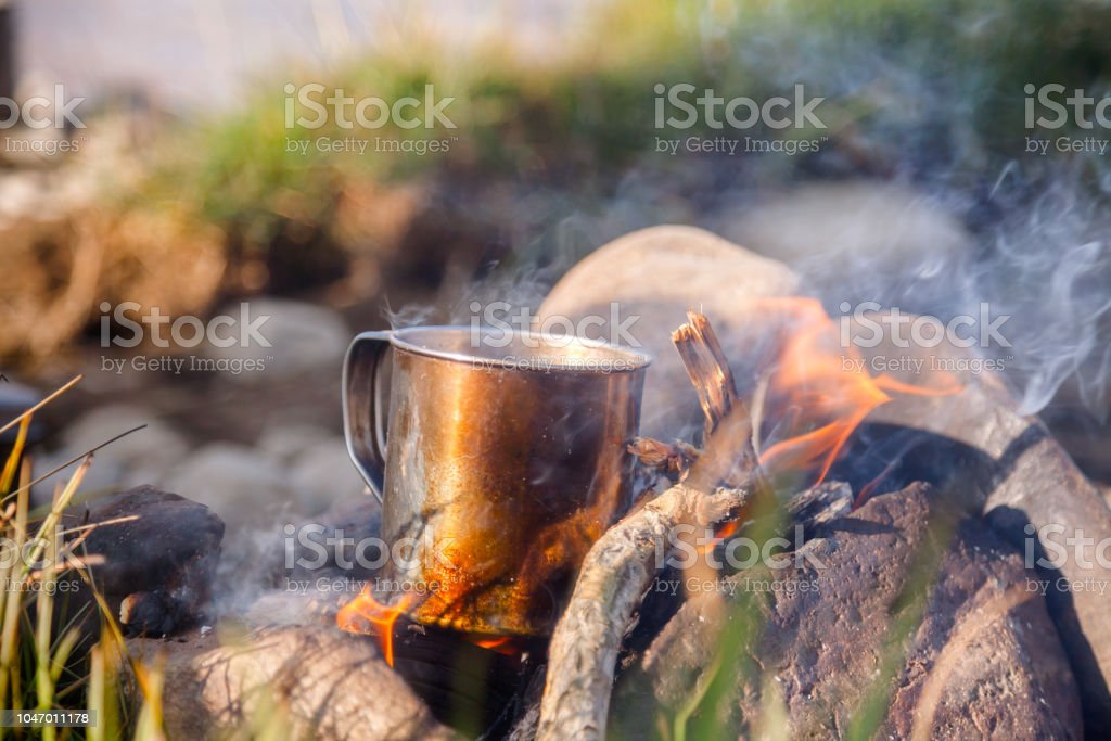 Warming cup of tea on open fire at wild camping stock photo