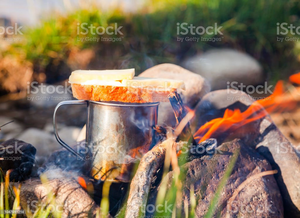 Warming cup of tea with sandwich on open fire at wild camping stock photo