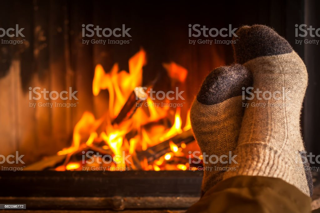 warming feet at fireplace stock photo