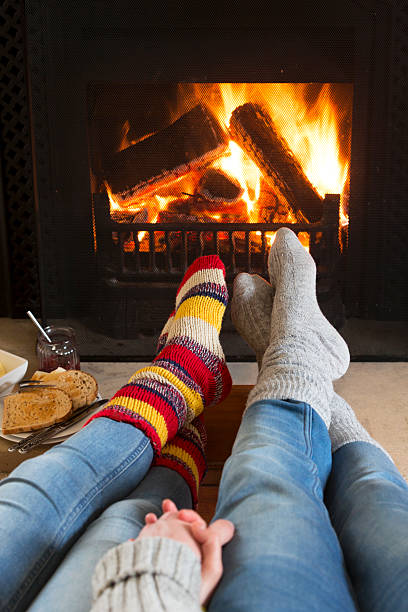 Warming Feet by the Fire Two people are sitting with their legs infront of a fire holding hands. They are wearing wooly socks and jeans, and have one foot crossed over the other. They are sitting with their legs stretched out in a lounge. There is toast and jam on the table. log fire stock pictures, royalty-free photos & images