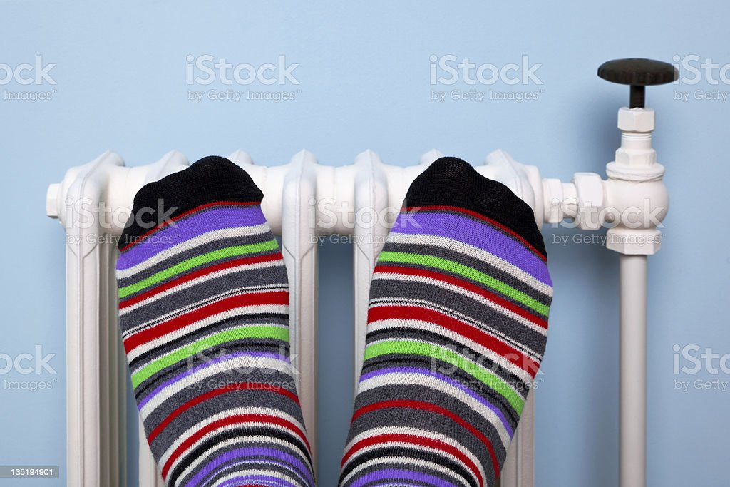 Warming feet on the radiator royalty-free stock photo