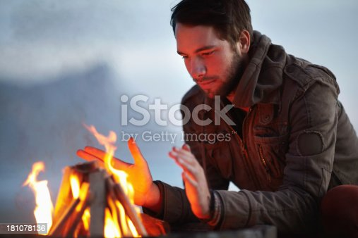 Handsome young man sitting by an open fire
