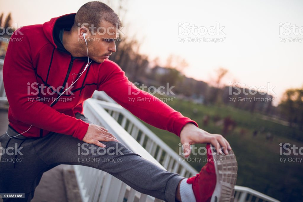 Young man is warming up and stretching before jogging.