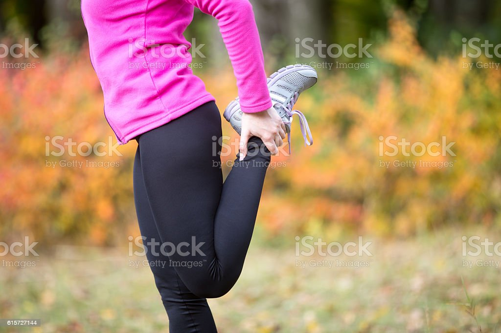 Warming up outdoors in the fall. Quadriceps standing stock photo