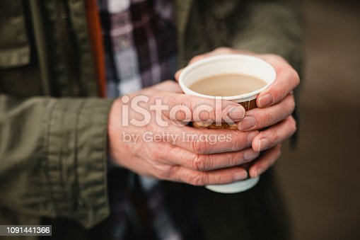 Close-up of an unrecognisable senior man holding a cup of tea to keep his hands warm in winter.