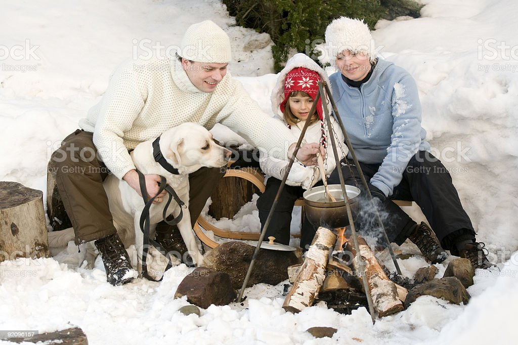 Warmly Dressed Family Having A Snowy Campfire With A Dog ...