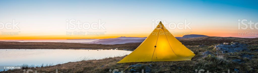 Yellow pyramid tent illuminated on a tranquil wilderness lake shore...